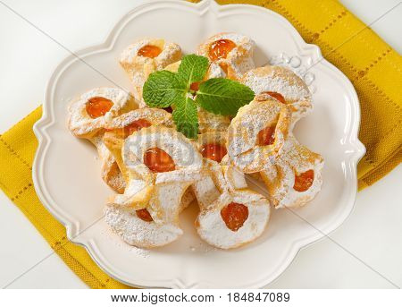 plate of tea cakes with apricot jam filling on yellow dishtowel