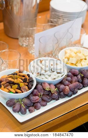 Grapes, yogurt pretzels, cheese, and trail mix as an appetizer snack at this wedding reception.