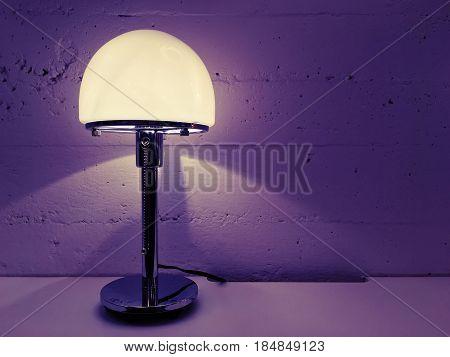 Contemporary design table lamp near concrete wall. Purple shades.