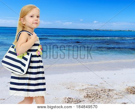 The little blonde girl in striped summer dress with beach bag on shoulder.White sand , blue sea and blue sky with clouds.