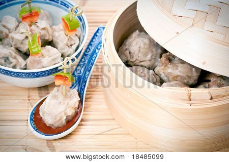 Traditional Chinese meal of dim sum or steamed dumplings on decorative spoon with harissa sauce and bamboo steamer