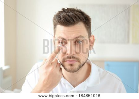 Young man putting contact lenses at home
