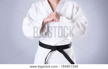 Young sporty woman in kimono on light background, closeup