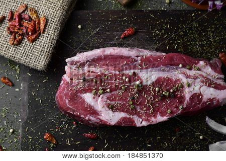 high-angle shot of a raw strip steak seasoned with different spices, such pepper corns of different colors, chili peppers or oregano, on a dark wooden chopping board placed on a rustic wooden a table