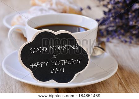closeup of a black cloud-shaped signboard with the text good morning and happy mothers day written in it, next to a cup of coffee on a table set for breakfast with some viennoiseries in the background