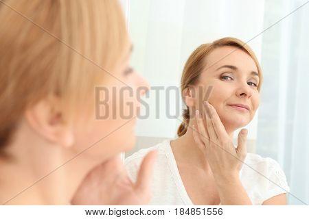 Happy senior woman applying anti-aging cream near mirror