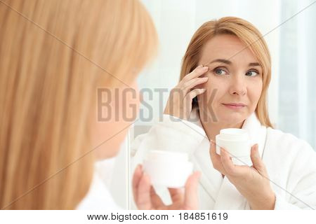 Happy senior woman applying anti-aging cream near mirror