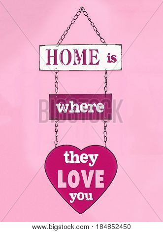 Home is where they live you sign hanging on pink wall