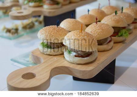 Cheeseburger Sliders with Lettuce Tomato and Cheese on wood