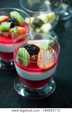 Delicious fruit jelly ontop wild strawberries blackberries kiwi slice