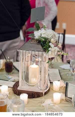 Wedding reception centerpiece with a location seating sign, candles, and flowers ont he table.