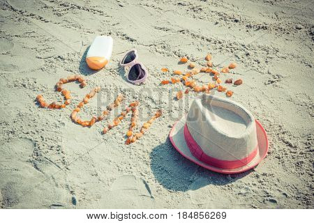 Word And Shape Of Sun, Sunglasses, Sun Lotion And Straw Hat On Sand At Beach, Summer Time