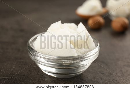 Shea butter in glass bowl on table, close up