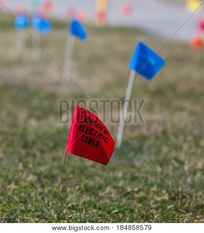 Utilities Location Flag Marking Underground Water, Electric, Telephone, Cable, Gas and Sewer Lines.
