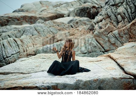 young beautiful woman with tarot cards in her hands with stone background