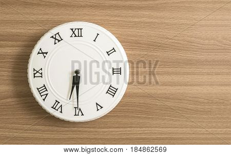 Closeup white clock for decorate show half past six or 6:30 a.m. on wood desk textured background with copy space