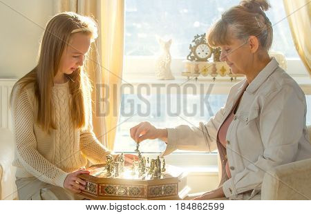 Little girl and pension age woman playing playing chess in the domestic environment. People agains sun light. Educational concept