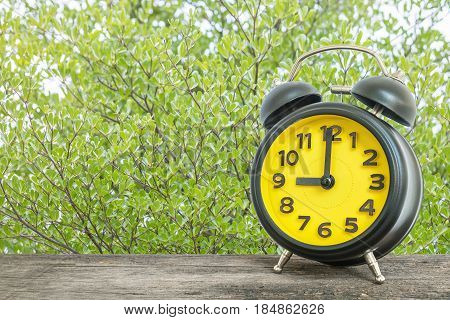 Closeup black and yellow alarm clock for decorate in 9 o'clock on old brown wood desk on green leaves in the park textured background