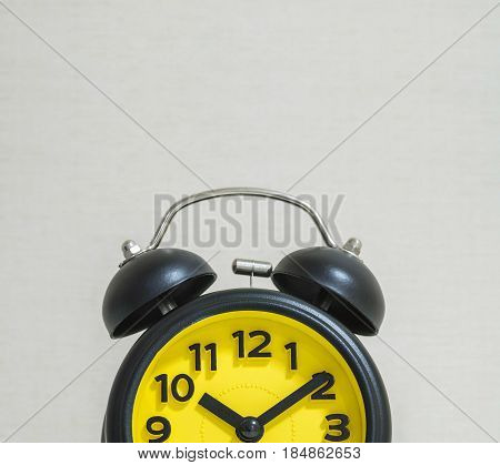Closeup part of black and yellow clock for decorate in ten past ten o'clock on blurred wallpaper wall textured background with copy space