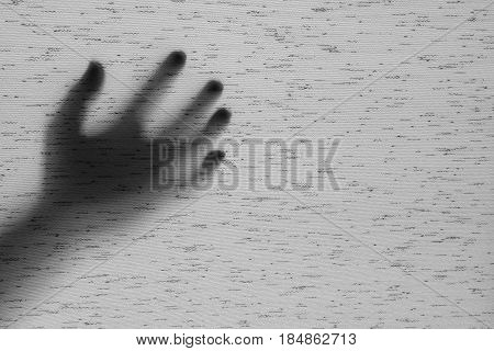 Closeup surface shadow of hand behind gray fabric curtain textured background with copy space in black and white tone in horror concept