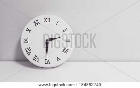 Closeup white clock for decorate show half past two o'clock or 2:30 p.m. on white wood desk and wallpaper textured background in black and white tone with copy space