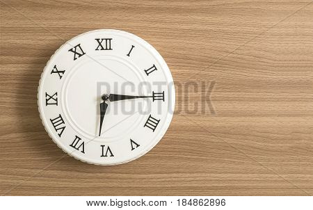 Closeup white clock for decorate show a quarter past six or 6:15 a.m. on wood desk textured background with copy space