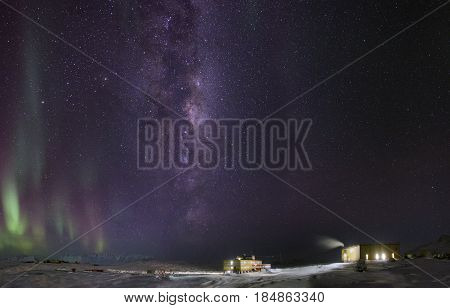 Northern Lights and the Milky Way in the starry sky. View of Antarctica. Night.