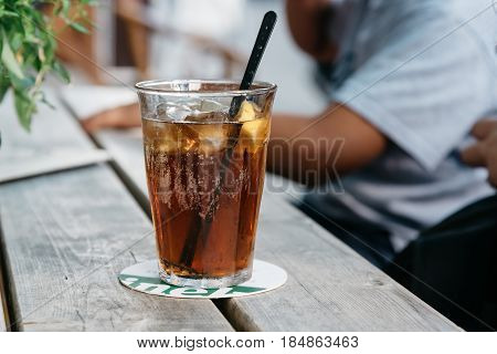 Refreshing glass of cola on wooden table in a bar.