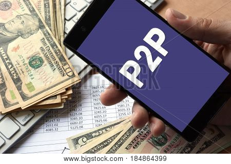 Smartphone in hand with message P2P. Peer to peer lending concept.