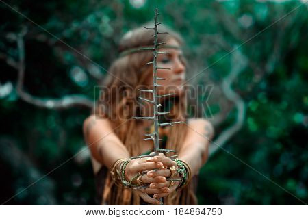 portrait of beautiful shaman woman holding branch with thorns in her hands. Focus on the branch