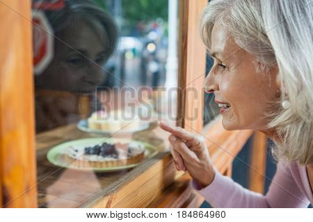 Close  up of senior woman looking at food through glass window of coffee shop