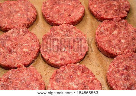Fresh raw juicy unprepared beef burger patties on brown paper background
