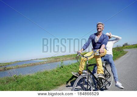 Cheerful couple riding bike on a sunny day