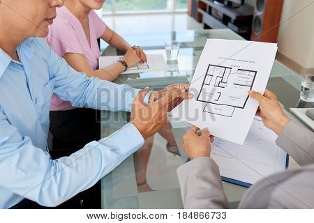 Apartment floor plan in hands of client and estate agent