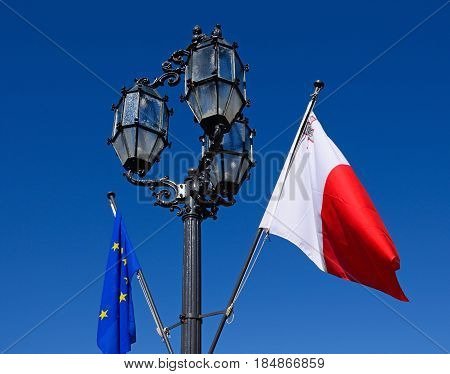 Wrought iron streetlight with the Maltese flag and European Union flag in Castille Square Valletta Malta Europe.