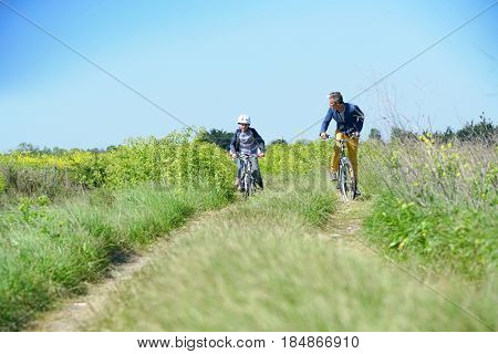 Father with kids riding bicycle in countyside