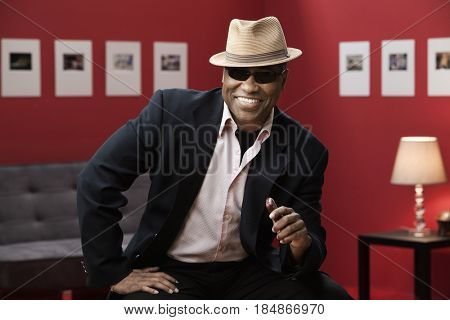 Smiling black man in suit, sunglasses and hat