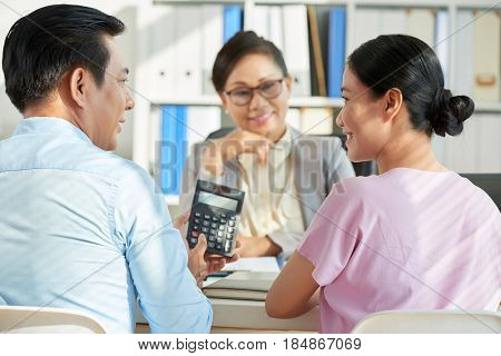 Vietnamese man showing loan amount on calculator screen to his wife