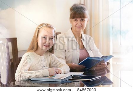 10 years old girl and her teacher. Little girl study during her private lesson. Tutorial and educational concept.