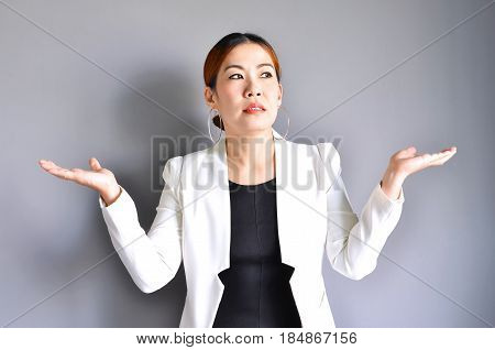 Asian business woman raising her hands on both sides on a gray background.