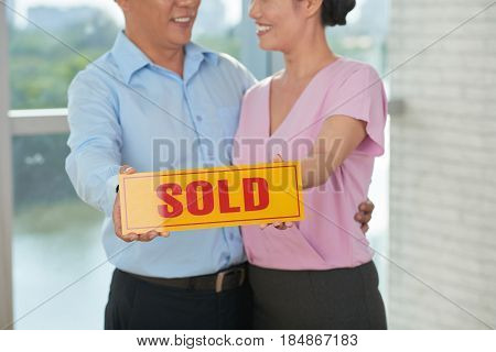 Happy couple holding sold card, as they have bought a house