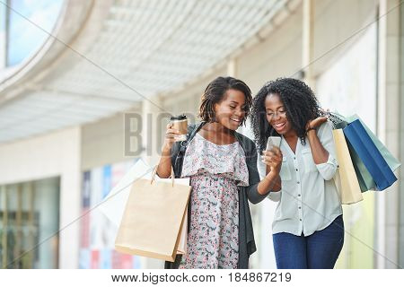 Laughing women looking at some funny photo on smartphone screen