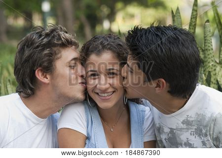 Hispanic men kissing woman