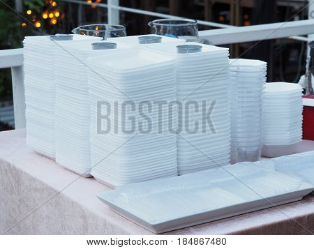 Set of disposable tableware for dinner party. Pile of white foam dishes transparent plasic glasses and spoons on table.