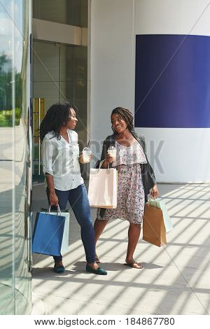Cheerful women with paper-bags walking out of shopping mall