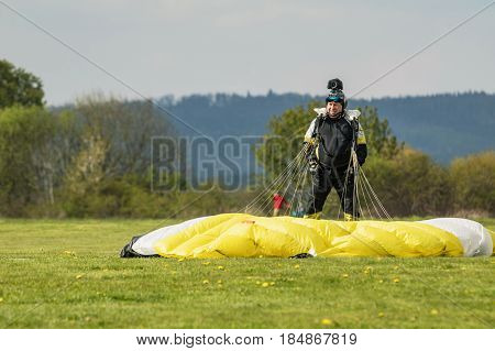 PRIBRAM CZECH - APRIL 30 2017. The parachutist with a yellow parachute landed on the grass. Skydiver in a black jumpsuit with glasses is a yellow parachute.