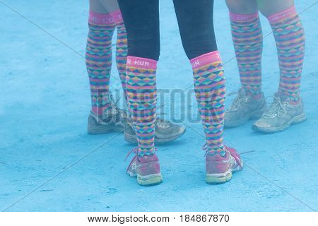 STOCKHOLM SWEDEN - MAY 22 2016: Legs with colorful socks and blue color powder on the ground in the Color Run Event in Sweden May 22 2016