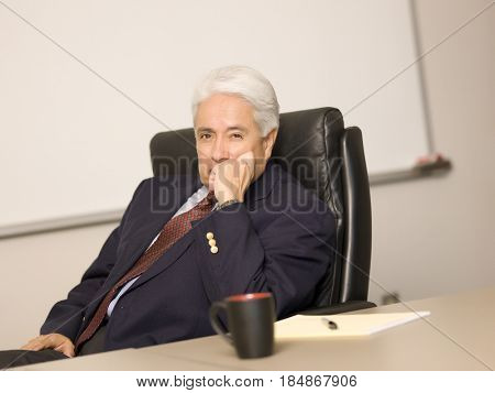 Hispanic businessman sitting at desk