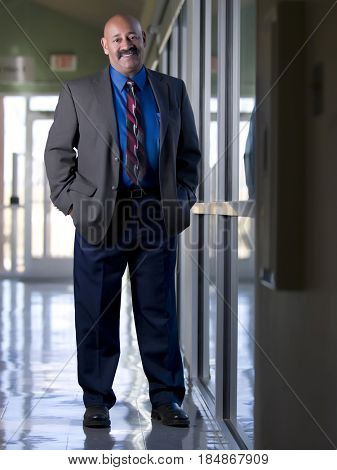 Hispanic businessman standing in office corridor