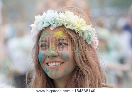 STOCKHOLM SWEDEN - MAY 22 2016: Face of smiling young beautiful woman with color dust in her face and flowers in the hair in the Color Run Event in Sweden May 22 2016